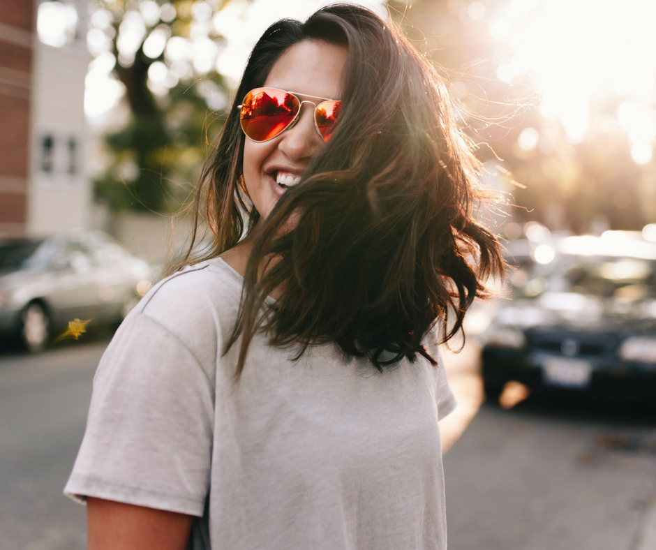 woman outside with sunglasses smiling happy and healthy
