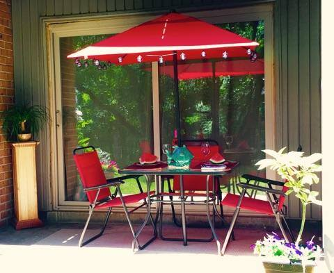 table and chairs with a decorated umbrella on an apartment balcony
