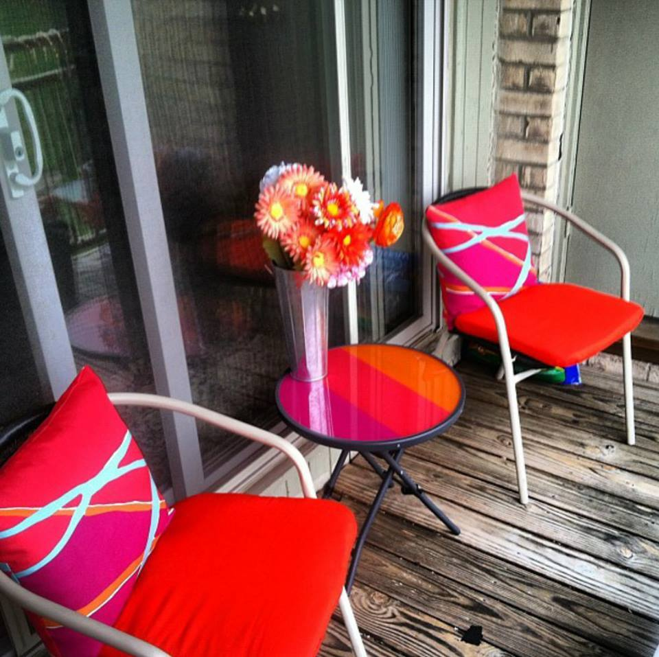 balcony table and chairs with red cushions
